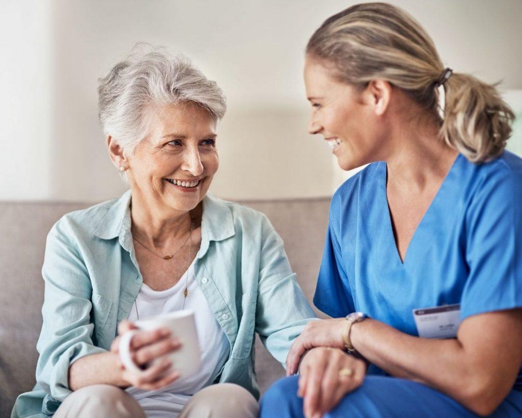 Pflegerin und Klientin lachen gemeinsam.